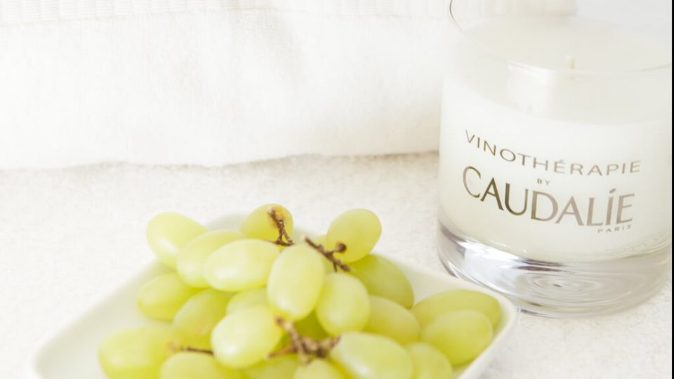 Caudalie treatment candle next to a bunch of grapes